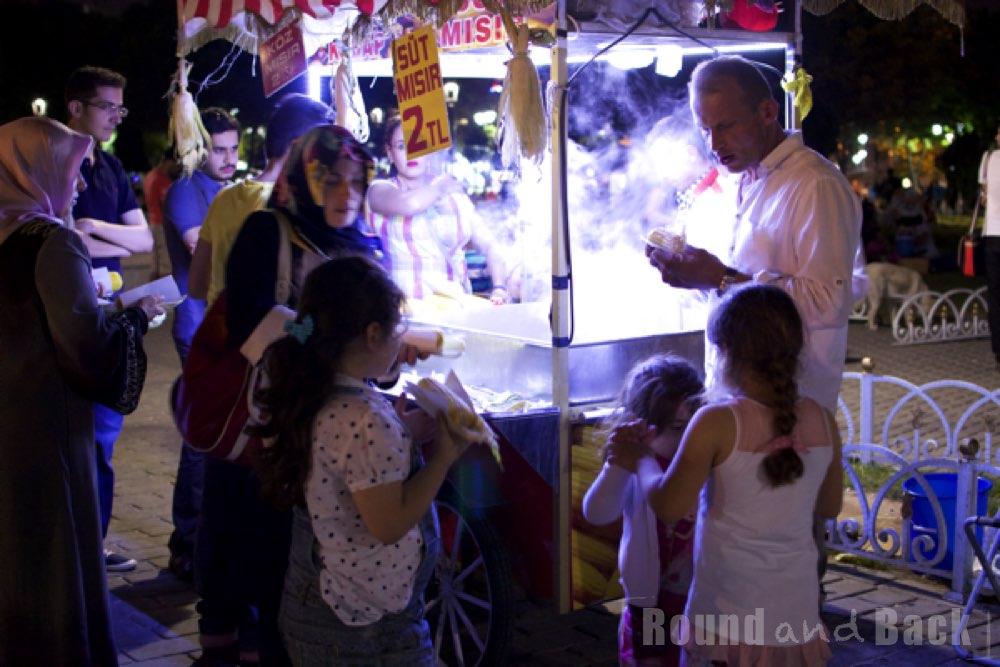 Maisverkäufer am späten Abend, umkreist von Kindern und Erwachsenen, Streetfotografie