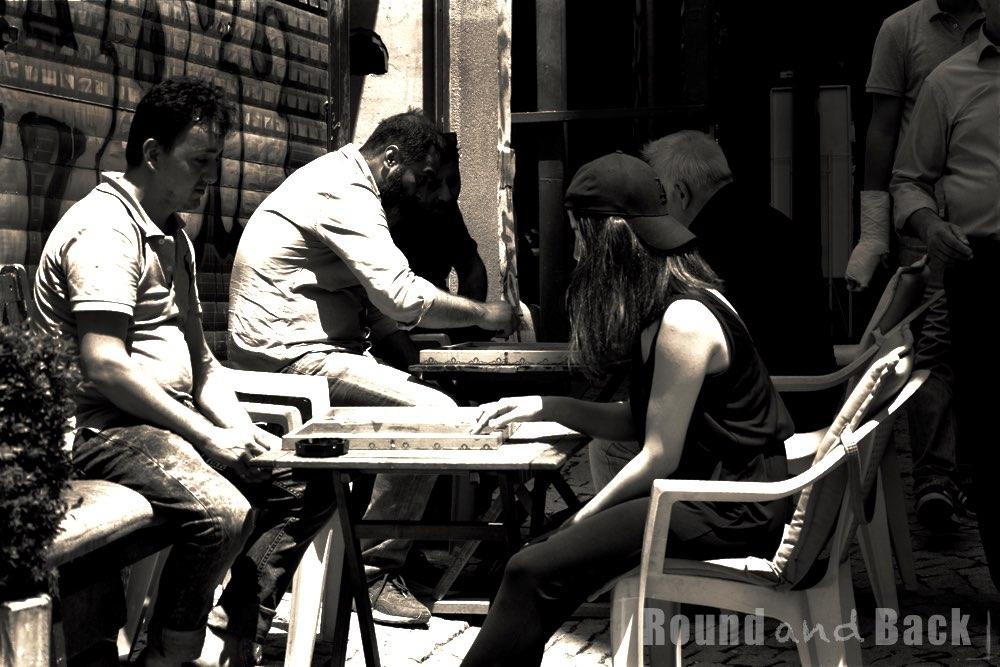 Zwei junge Erwachsene spielen Backgammon, während sie in der Sonne sitzen Streetfotografie