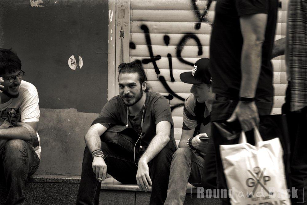 Junge erwachsene, die an einer Straßenseite sitze  und sich bei einer Zigarette unterhalten