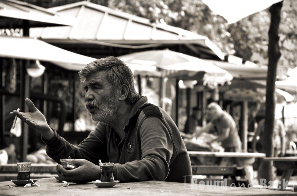 Älterer Mann der in einer angeregten Unterhaltung steckt, Streetfotografie