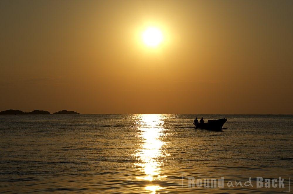 Zwei Fischer machen sich mit der aufgehenden Sonne auf den Weg zur Arbeit