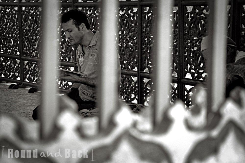 Ein Mann sitzt hinter eine vergitterten Absperrung und ist in sein Gebet vertieft
