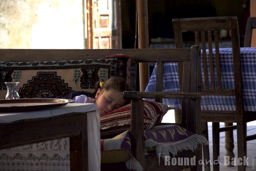 Ein kleines Mädchen, das auf der Bank eines Kaffes seelenruhig eingeschlafen ist