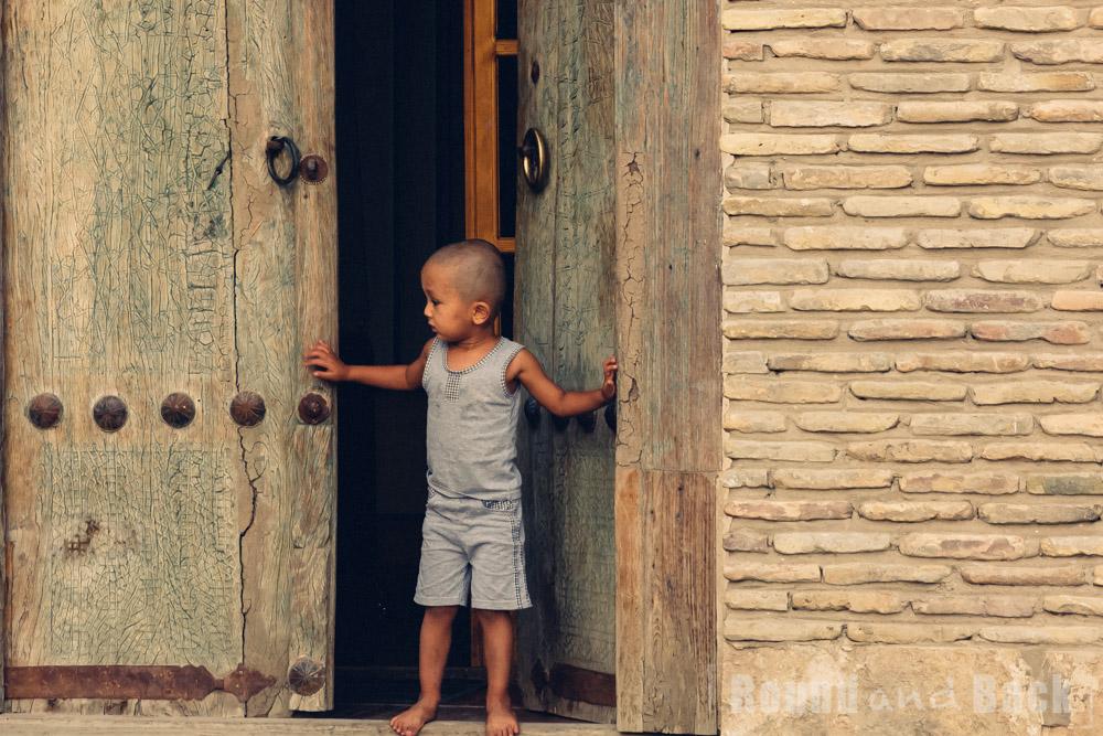 Kleiner Junger der vor den schweren Eingangstoren zu seinem Zuhause steht. Samarkand, Usbekistan.