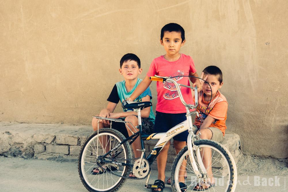 3 Jungs sitzen an der Straßenseite, einer mit Fahrrad. Samarkand, Usbekistan.