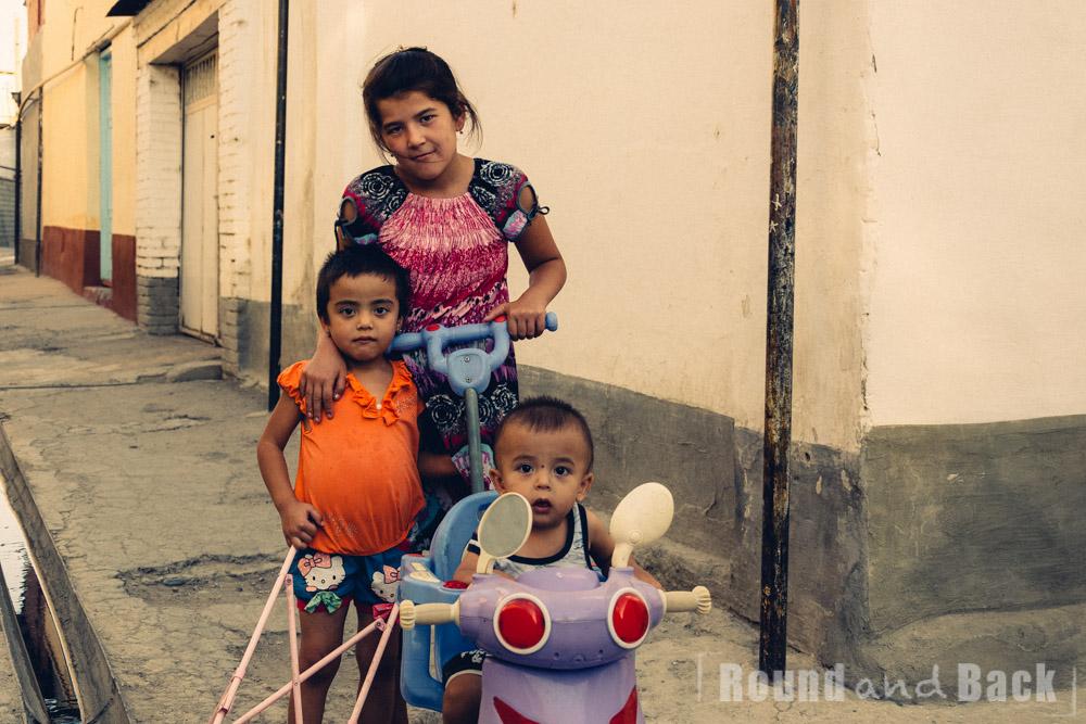 Mädchen geht mit ihrer kleinen Schwester und dem kleinen Bruder spazieren. Samarkand, Usbekistan.