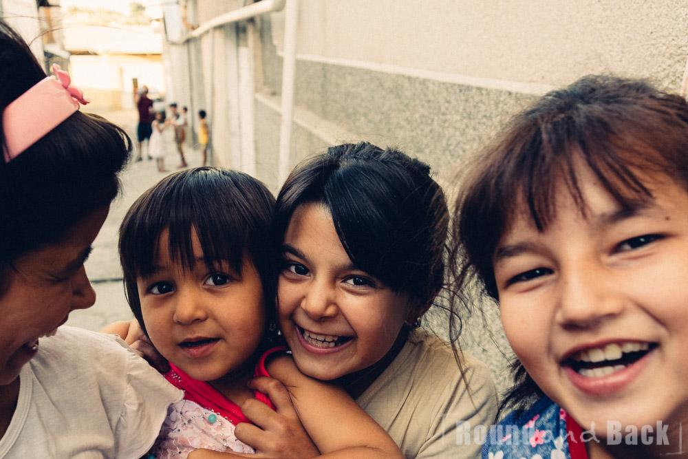 3 Mädchen, eine hebt ihren kleinen Bruder hoch, damit er meine Kamera sehen kann. Samarkand, Usbekistan.