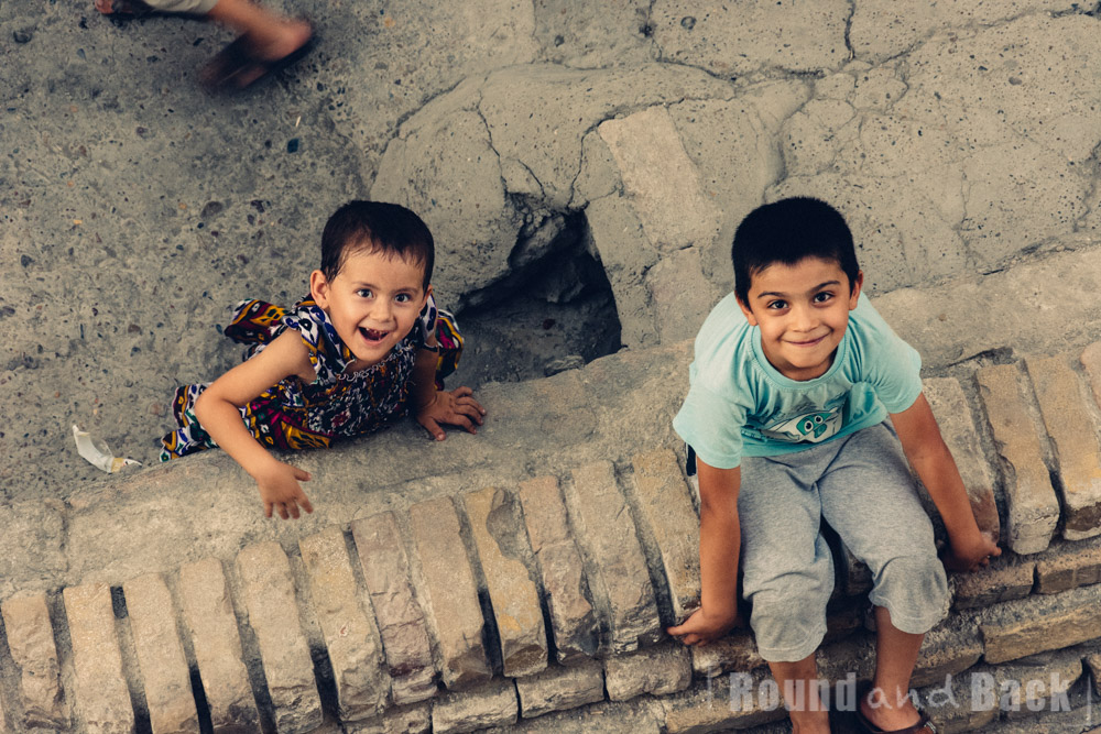 Bruder und Schwester, Aufnahme aus oberem Stock nach unten. Samarkand, Usbekistan.