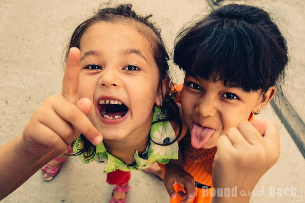 Zwei Mädchen, die mit frechen Gesten in die Kamera lachen. Samarkand, Usbekistan.