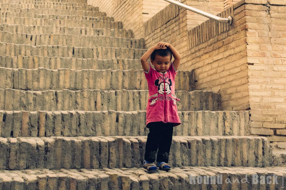 Junges Mädchen, das auf einer Treppe steht. Samarkand, Usbekistan.