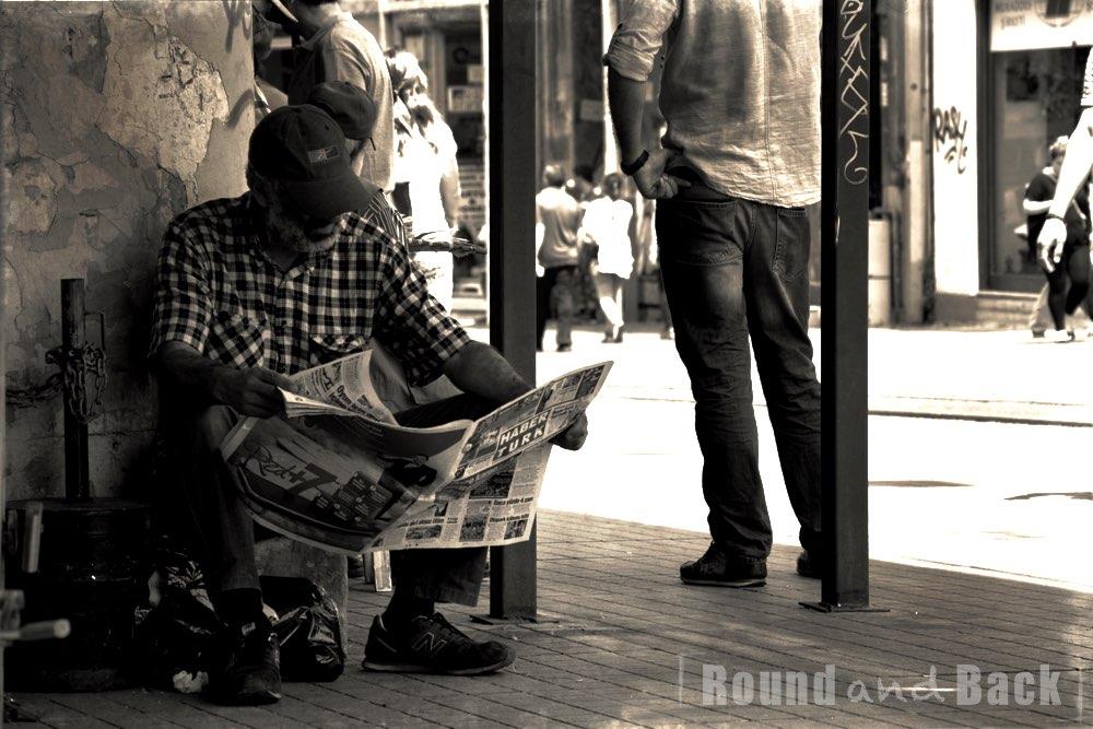 Älterer Mann, der es sich auf der Straße bequem gemacht hat und Zeitung liest, Streetfotografie
