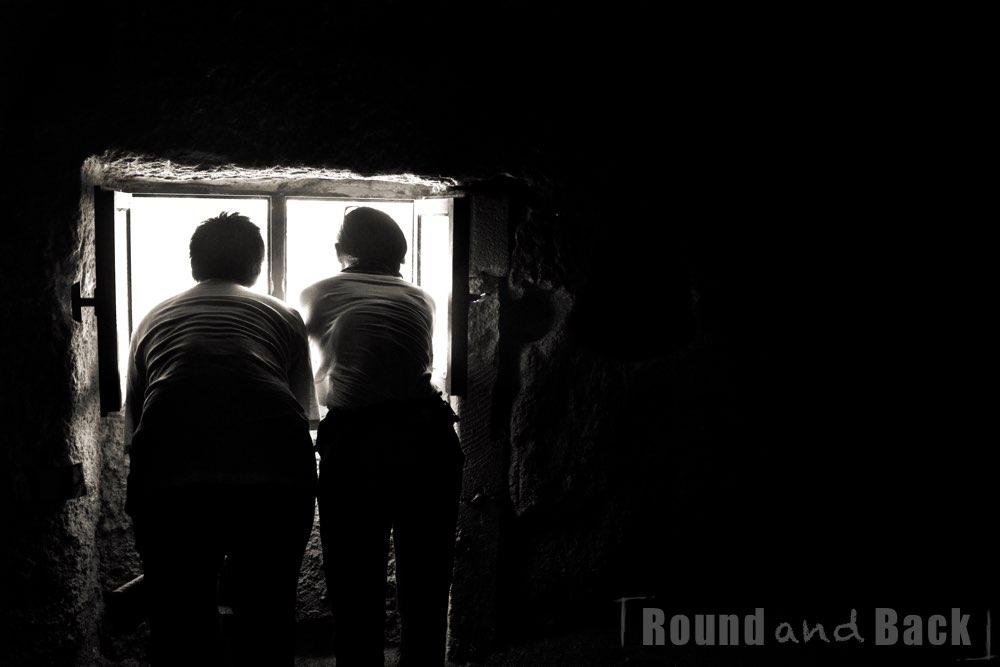 Ein Paar schaut dich ein Fenster aus einer Höhlenwohnung in Kappdokien, Streetfotografie