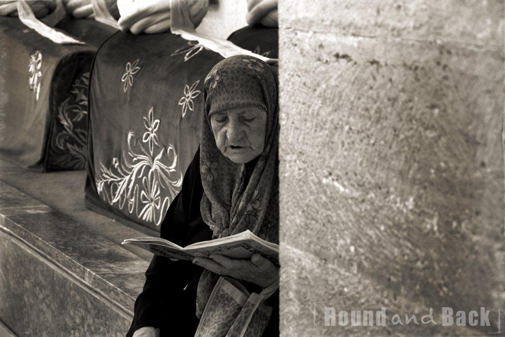 Eine alte Frau die in einer Mauernische sitzt und in ihr Gebet vertieft ist